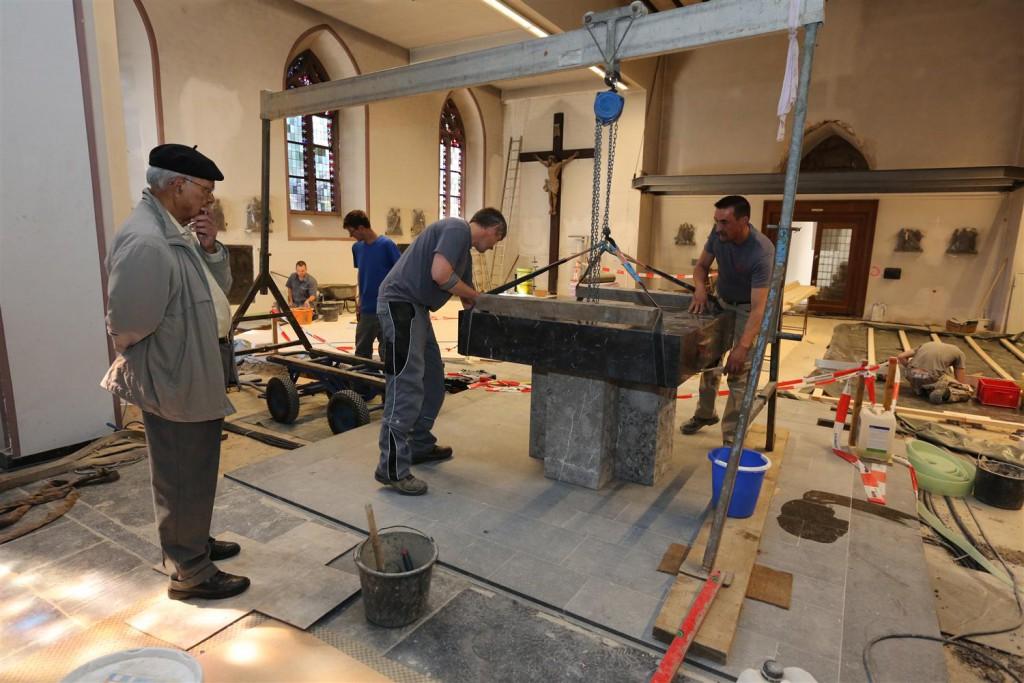 Pfarrer Francis Chirayath (links) beobachtet, wie der Altar in der Konzener Pfarrkirche wieder aufgestellt wird: Die Umbauarbeiten gehen gut voran, so dass das Ergebnis bald besichtigt werden kann. Foto: A. Gabbert